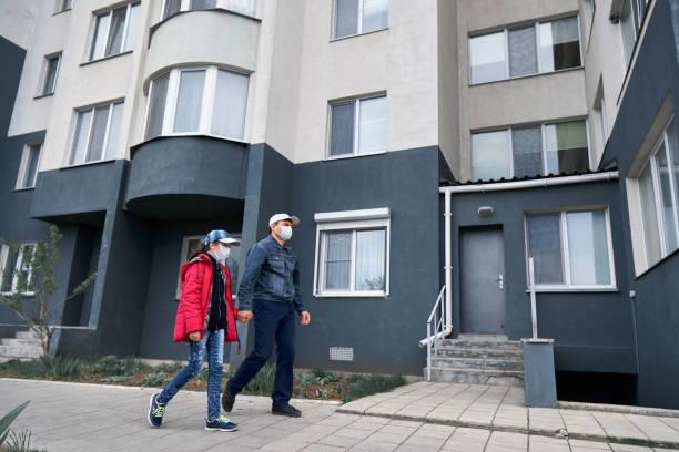 hombre y niña camina cerca de la pared de edificios de gran altura con apartamentos, padre e hija, una zona residencial, una máscara médica en sus rostros protege contra virus y polvo - foto de stock