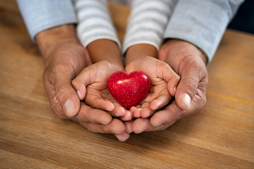 Family holding small red heart in hands on wooden background. Top view of father and daughter hands protect heart. High angle view of indian man and little girl hands holding red heart: adoption foster family, hope, gratitude and insurance concept