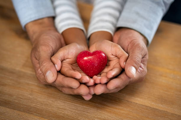 Man and child hand holding red heart stone stock photo