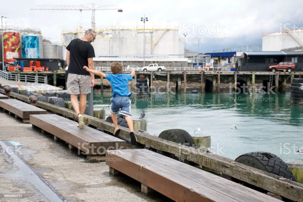 Man and Child Jumping from Seat to Seat in Harbour Area stock photo