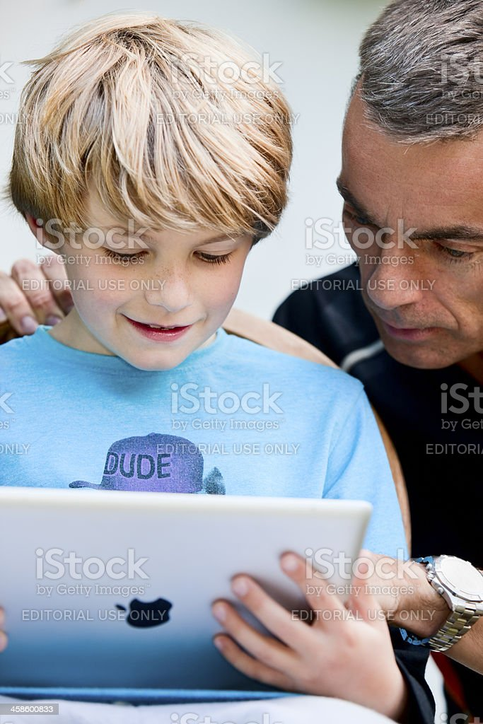 man and child looking at the screen of an iPad royalty-free stock photo