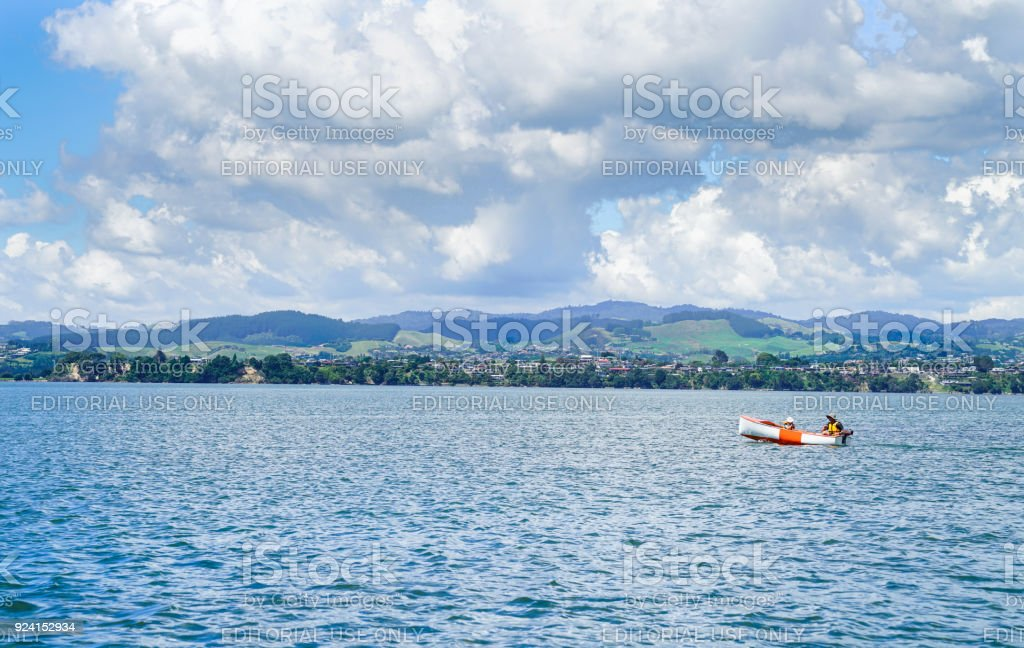 Man and child motoring in small orange and white dinghy. stock photo
