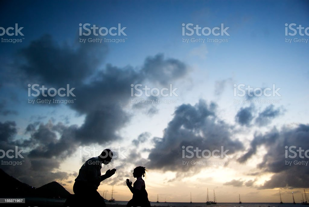 man and child praying together royalty-free stock photo