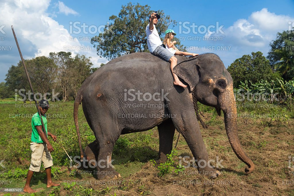 Man and child riding on the back of elephant stock photo