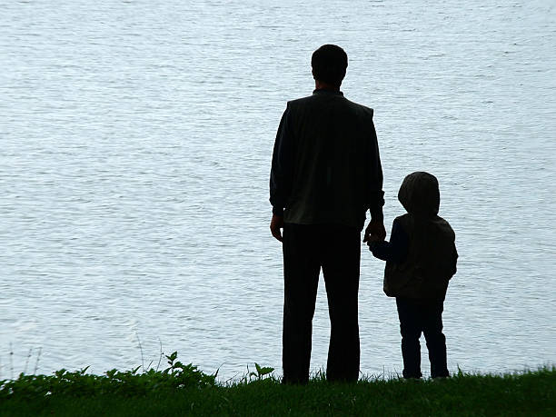 Man and child silhouette at evening stock photo