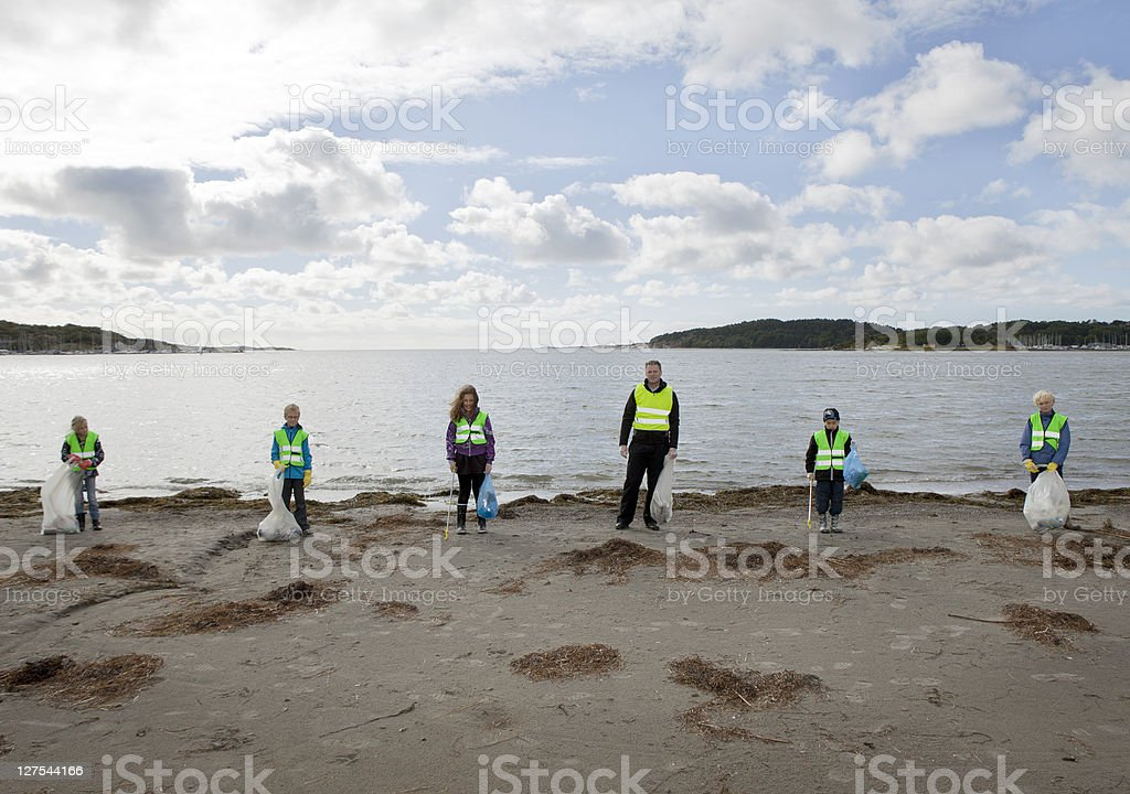 Man and children cleaning beach stock photo