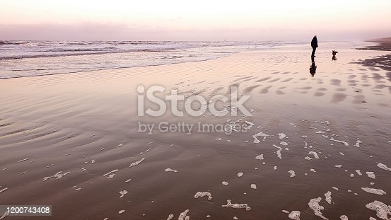 Sunset on the beach on a cold day in the winter, man and welsh corgi dog hiking along the water's edge, waves and foam, Ameland a Frisian island in the Wadden sea.