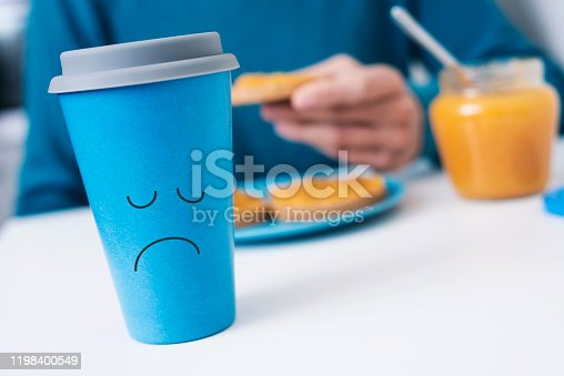 closeup of a blue cup of coffee with a sad face drawn in it on a white table and a caucasian man, wearing a blue sweater, in the background having the breakfast