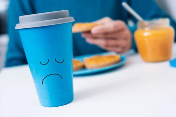 uomo e tazza di caffè con un viso triste a colazione - blue monday foto e immagini stock