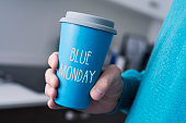 closeup of a young caucasian man, wearing a blue sweater, grabbing a blue cup of coffee with the text blue monday written in it