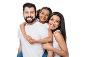 man and daughter piggybacking while woman standing near by isolated on white