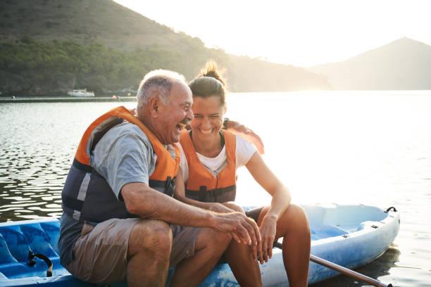 Man and daughter with arm around sitting on kayak stock photo