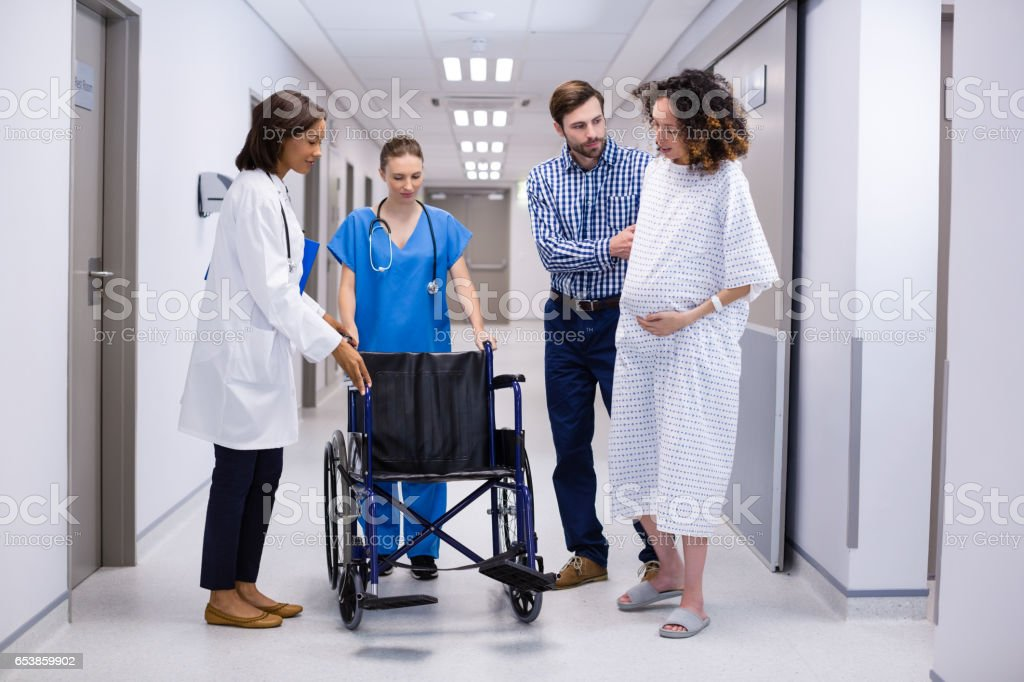 Man and doctors assisting pregnant woman to sit on wheelchair stock photo