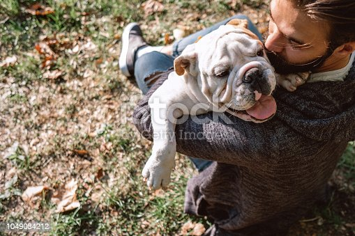Handsome Bearded Man And His Bulldog Spending Free Time At Park On Sunny Day