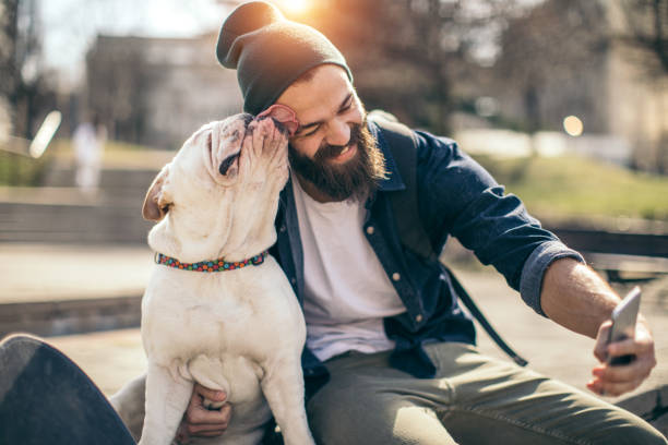 man and dog in the park - beard stock pictures, royalty-free photos & images