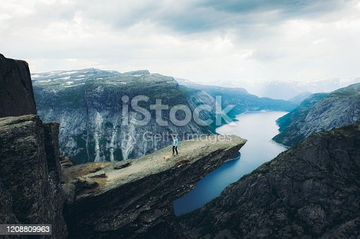 Young man hiker and his small cute dog - pug breed feeling freedom and happiness sitting on the cliff at the edge of the Trolltunga mountain enjoying the view of dramatic sunrise above the fjord in Norway
