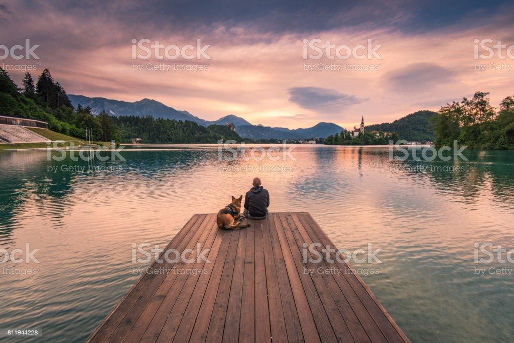 Mensch und Hund sitzt auf der Holzterrasse am Bleder See, Slowenien – Foto
