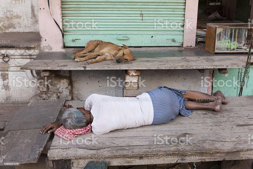 Man and dog take a nap in front of store foto