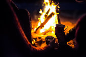 man and girl sit around campfire at night with cups