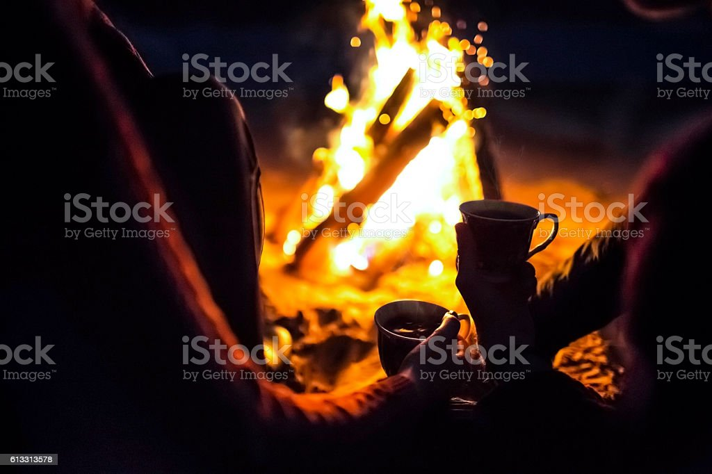 man and girl sit around campfire at night with cups stock photo