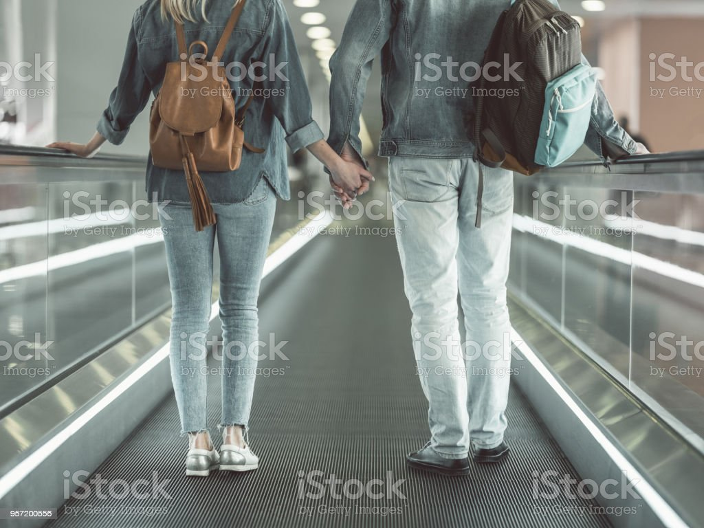 Man and girl standing on moving staircase stock photo