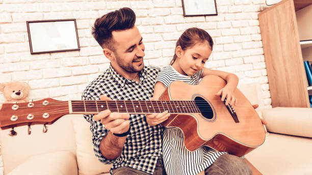 Man and Girl Together Play Guitar in Apartment. stock photo