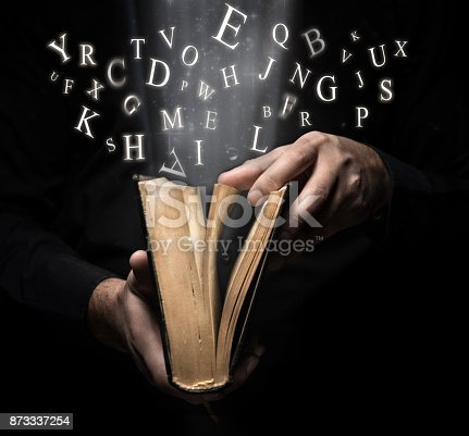 istock Man and Glowing letters on book light 873337254