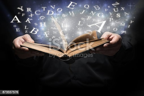 istock Man and Glowing letters on book light 873337576