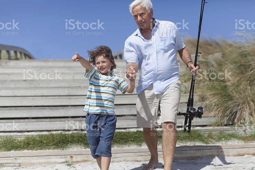 Man and grandson with fishing poles stock photo