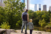 Man and his charming little son admire the views in Central Park, New York. Quality family time.