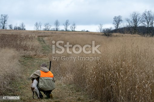 A hunter bend down affectionately to praise hunting dog for good work on a rainy fall morning.