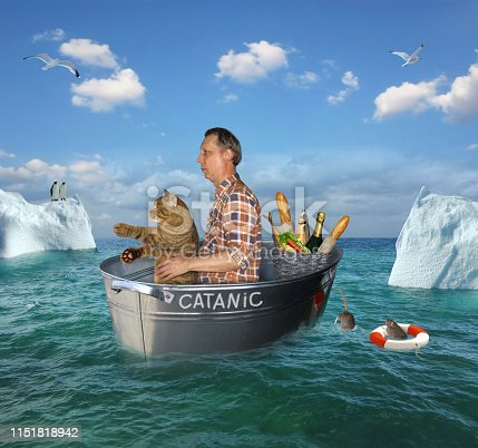 The man and his cat are drifting in the steel wash tub after the shipwreck among the icebergs in the high seas. Their lifeboat is called Catanic.