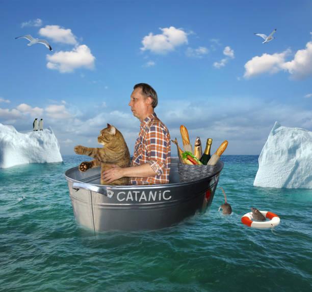 man and his cat drift in a washtub - bacinella metallica foto e immagini stock
