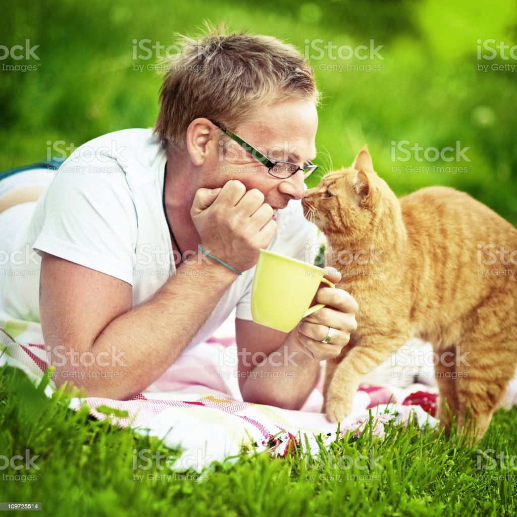 Man and his cat lying on the lawn royalty-free stock photo