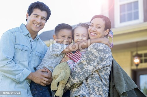 Smiling family look at the camera while embracing. The mom has returned from military assignment. The little girl is holding a small US flag.