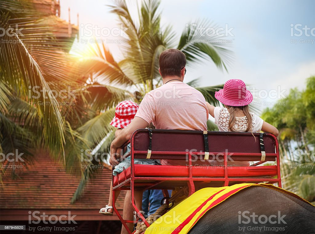 Man and his daughters riding on the back of elephant stock photo