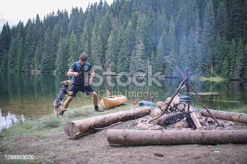 Man and his Yorkshire terrier dog are having fun while they are on camping at the mountains