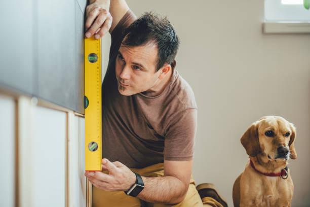 mann und hund machen renovierungsarbeiten zu hause - hundezubehör diy stock-fotos und bilder