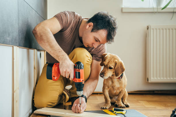 Man and his dog doing renovation work at home Man doing renovation work at home together with his small yellow dog drill stock pictures, royalty-free photos & images