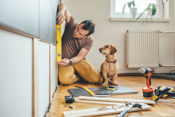 Man and his dog doing renovation work at home Man doing renovation work at home together with his small yellow dog home improvement stock pictures, royalty-free photos & images