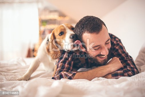 Young smiling man affectionate with his dog
