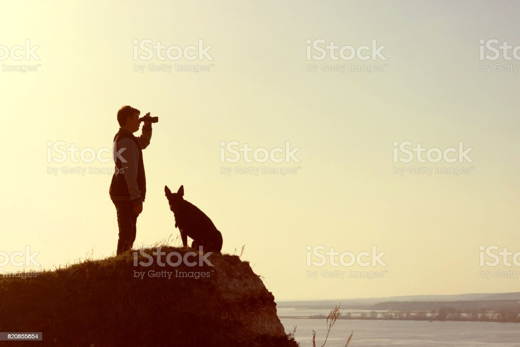 man and his dog stand on mountain peak stock photo