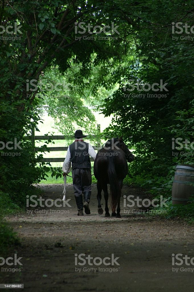 Man and his horse walk away stock photo