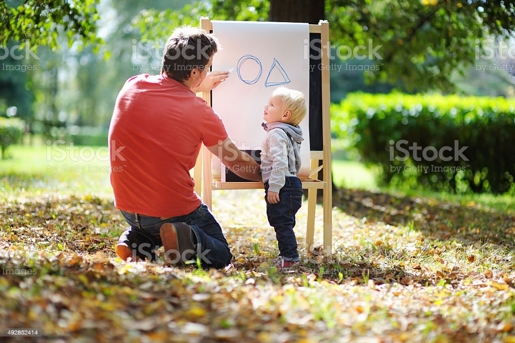 Man and his son at blackboard practicing geometry stock photo