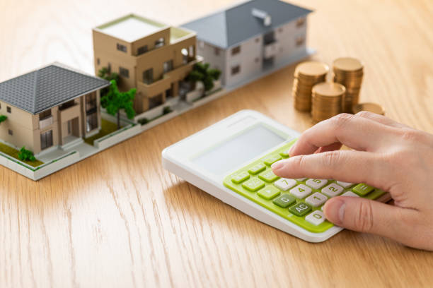 Man and house model calculating with calculator Man and house model calculating with calculator borrowing stock pictures, royalty-free photos & images