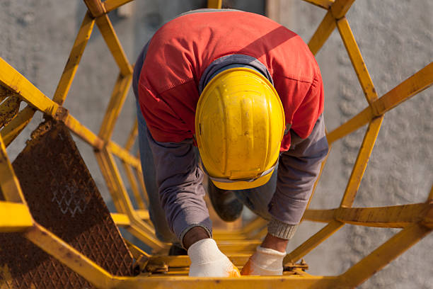 Man and Ledder A man climbing to a caged ladder. confined space stock pictures, royalty-free photos & images