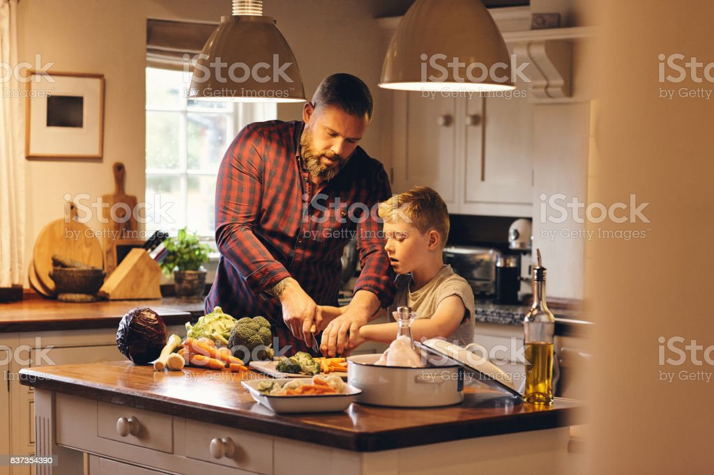 Man and little boy cutting fresh vegetables in kitchen stock photo