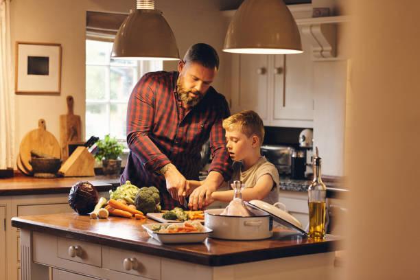 mann und kleiner junge schneiden frisches gemüse in der küche - hausmannskost stock-fotos und bilder