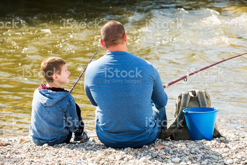 Man and little boy fishing stock photo