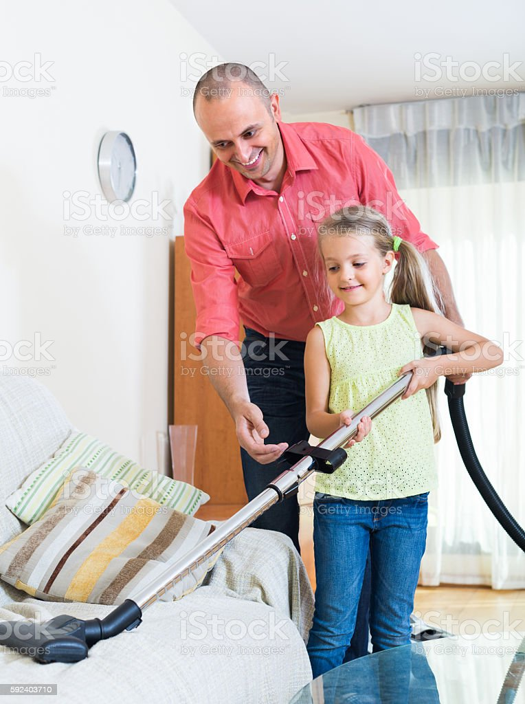 Man and little girl hoovering at home stock photo